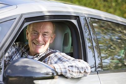 Portrait Of Smiling Senior Man Driving Car